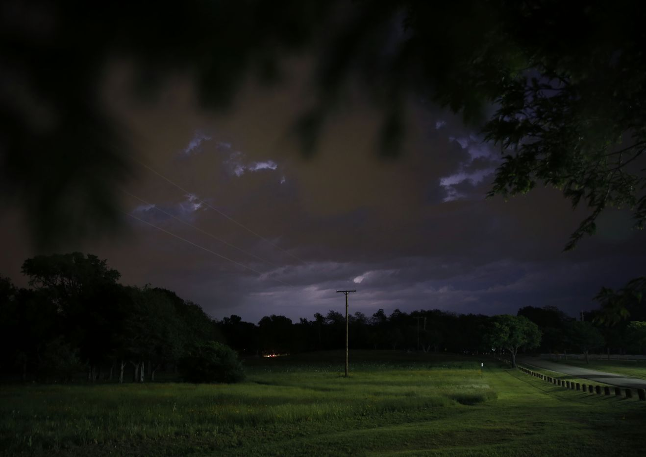 Lightning is seen in the distance to the northeast from Winfrey Point near White Rock Lake in Dallas on Friday, April 21, 2017.