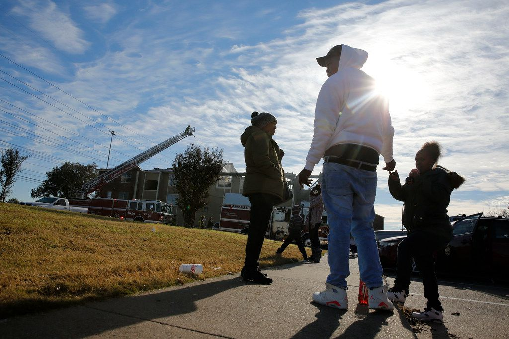 Linda Smith (from left), Courtney Turner and Jasmine Dixon wait to leave their complex during an apartment fire near the intersection of Interstate 635 and Ferguson Road in Dallas.