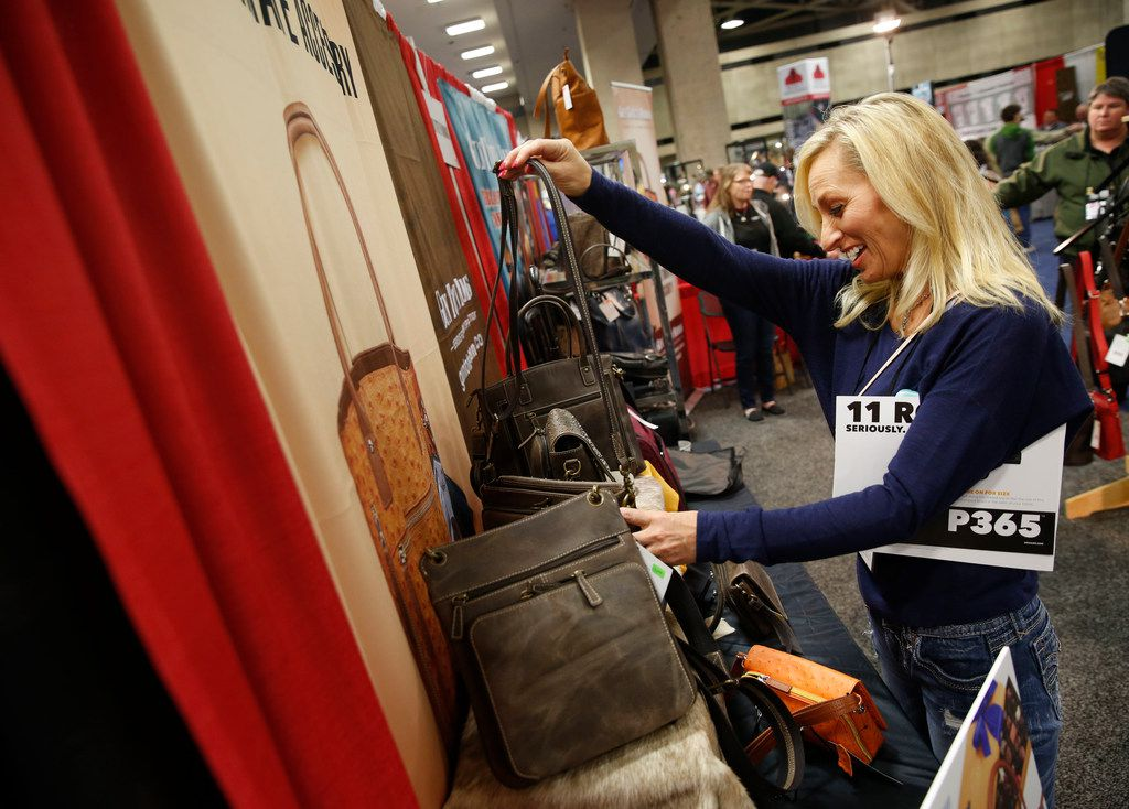 Rebecca Schneider looks at a concealed carry handbag at the NRA Annual Meeting & Exhibits at Kay Bailey Hutchison Convention Center in Dallas on Friday, May 4, 2018. (Rose Baca/The Dallas Morning News)
