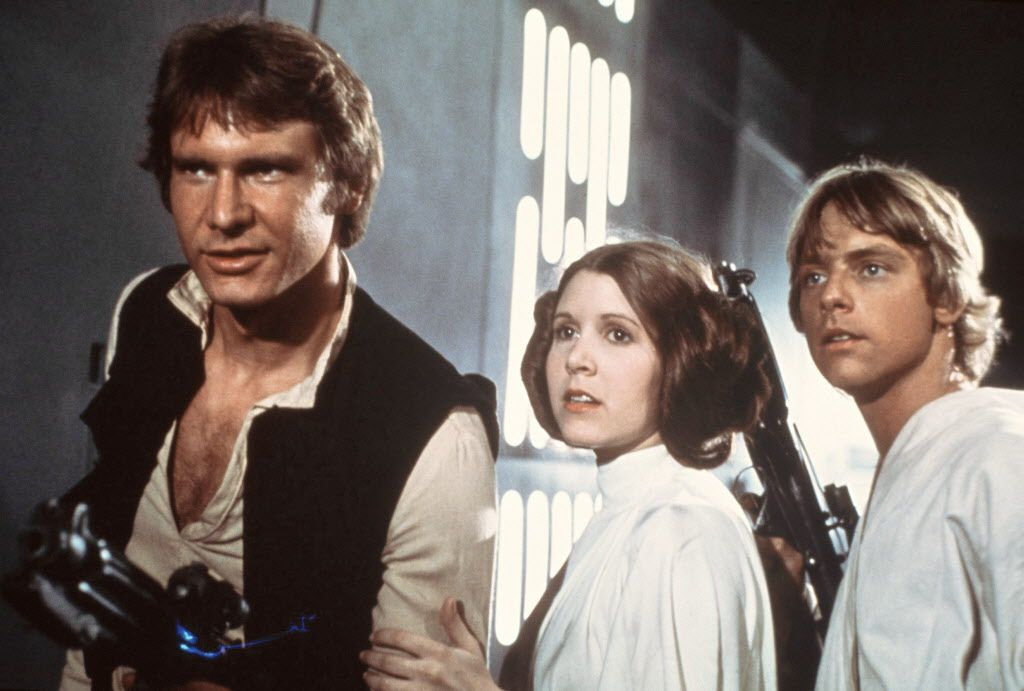 """This publicity film image provided by 20th Century-Fox Film Corporation shows, from left, Harrison Ford as Han Solo, Carrie Fisher as Princess Leia Organa and Mark Hamill as Luke Skywalker in a scene from the """"Star Wars"""" movie released by 20th Century-Fox in 1977."""