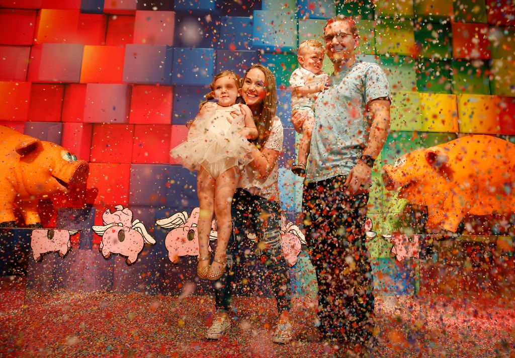 Vinny and Heather Torregrossa, and their children Emersyn, 4, and Lennon, 2, play in a cloud of confetti at Candytopia, an immersive pop-up art exhibit in Dallas. You can still get tickets now through Labor Day 2019.