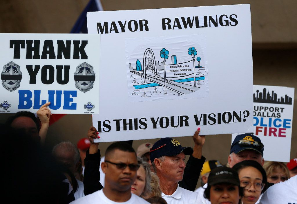 Dallas police and fire retirees hold signs during a rally against Mayor Mike Rawlings at City Hall on April 26, 2017.