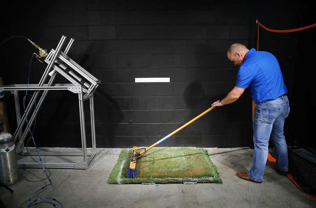 Technical manager Jeremy Dutton brushes coconut filing into a turf sample before firing a baseball at it in the Shaw Sports Turf's indoor performance lab in Dalton, Georgia, Monday, November 19, 2018.  The Texas Rangers are considering using Shaw's B1K playing surface for Globe Life Field which is under construction in Arlington. (Tom Fox/The Dallas Morning News)