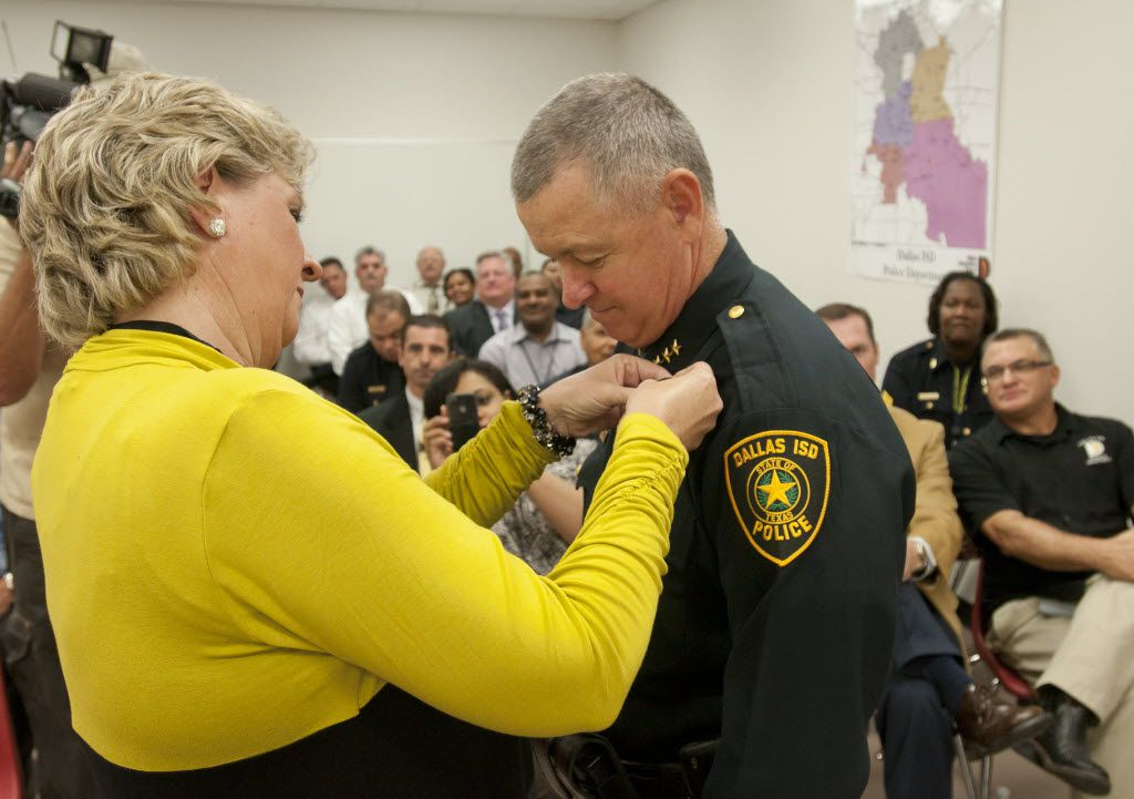 JoAnne Miller, left, pins a badge on her husband, Craig Miller, after he took the oath of office as the new police chief of the Dallas Independent School District during a ceremony at the department's  headquarters on Oct. 26, 2011.