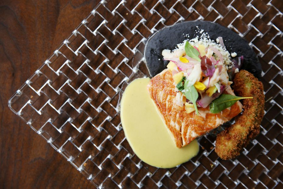 Seared king salmon with black bean-prosciutto refritos, aji-creamed-corn sauce, crab-mango ceviche and fried avocado is featured on Flora Street Cafe's lunch menu.