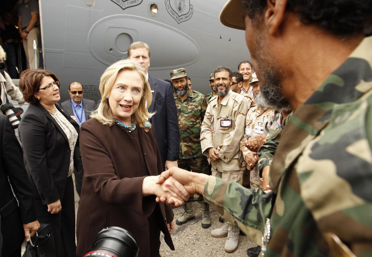 Secretary of State Hillary Clinton meets with American soldiers upon arriving in Tripoli, Libya for an unannounced visit, Oct. 18, 2011. Clinton was to meet with the leaders Washington hoped to install and encourage them to follow through on a promise of swift elections, but it would soon become clear that the task of unifying the country was beyond them.