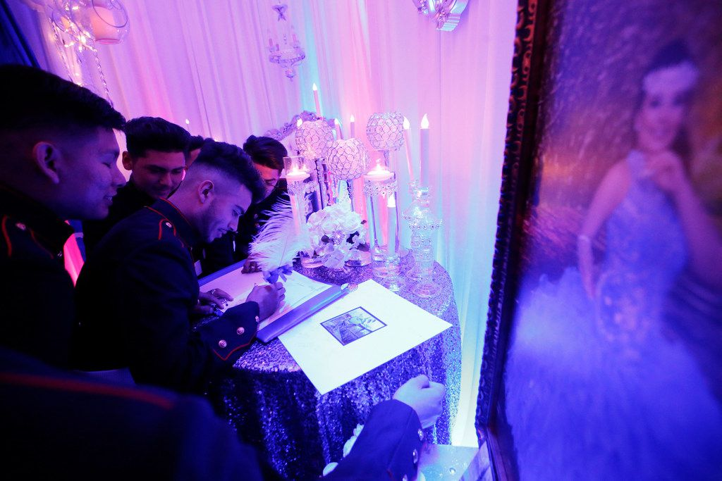 Members of the Latin Boyz Cadets sign the quinceañera's guest book.