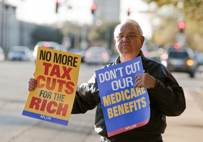 Tommy Christakis of Mansfield protests possible cuts to social security and medicare outside of Sen. John Cornyn's office in North Dallas.