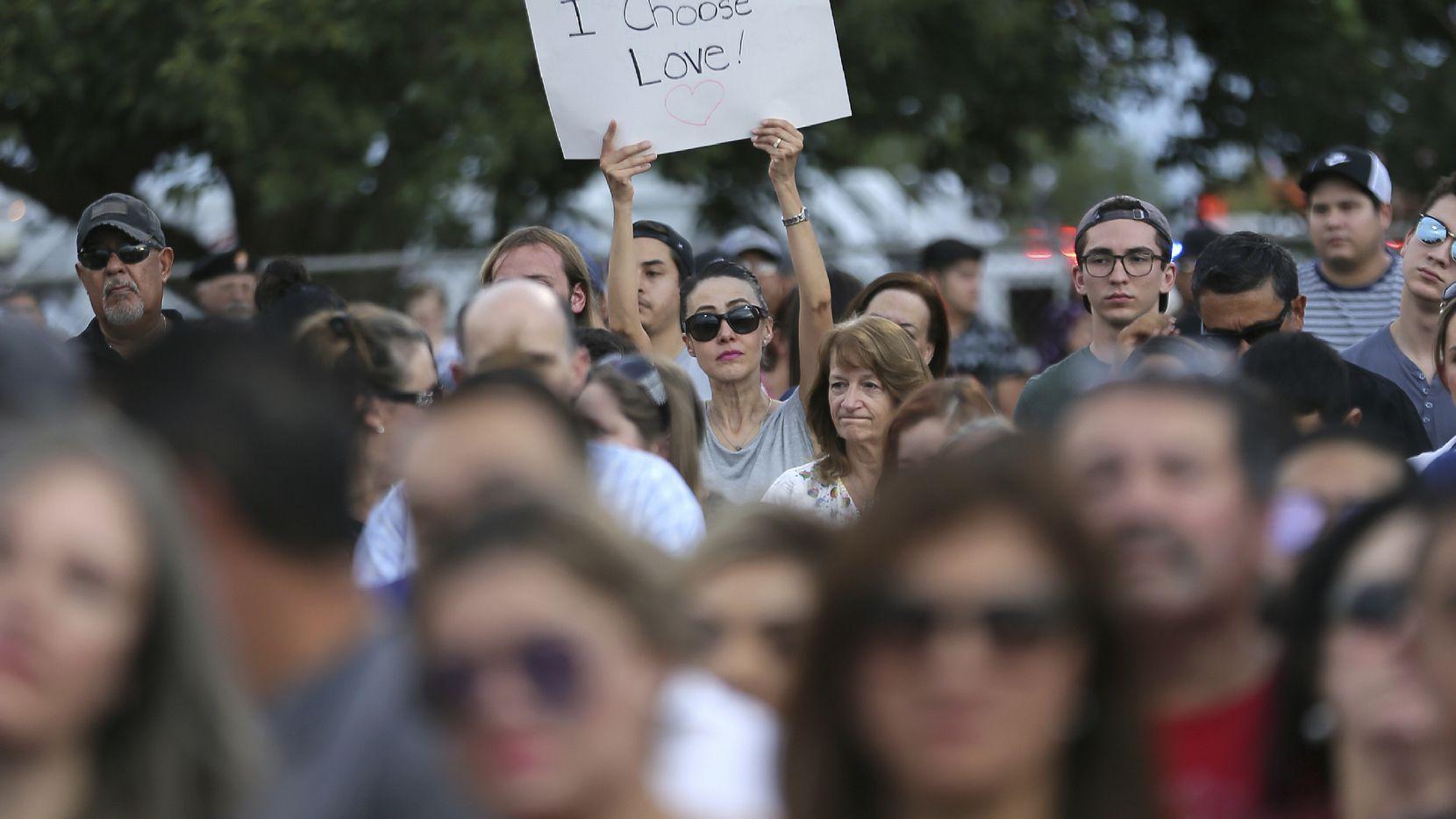 """Una persona porta una pancarta con la leyenda """"Yo escojo el amor"""" en una vigilia en El Paso, Texas."""