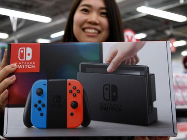 This file photo taken on March 3, 2017 shows 31-year-old Nao Imoto posing with her newly purchased Nintendo Switch game console at a shop in Tokyo.