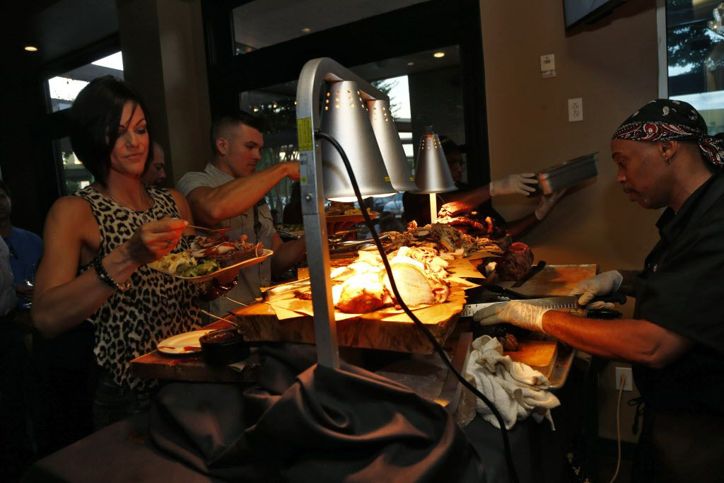 Danielle and Darren Natoni (left couple) are served barbecue by Robert Reese at Hickory, Kent Rathbun's new restaurant in Plano.
