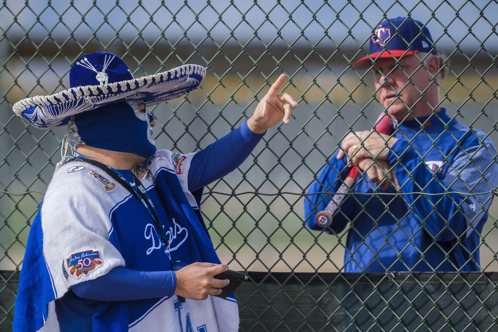 "Los Angeles Dodgers fan Carlos Morales chats with Steve Buechele, Texas Rangers special assistant for baseball operations, on a practice field during a spring training workout on Feb. 25 at the Rangers' facility in Surprise, Ariz.. Morales said he visited the Rangers camp for the day because, ""while the Dodgers are my team, baseball is my sport."""