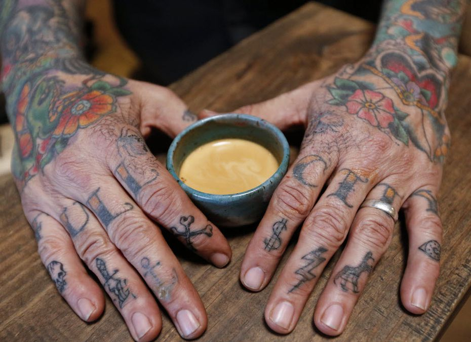 Michael Wyatt, owner of the Full City Rooster, has the name of his coffee roasting studio tattooed on his knuckles.