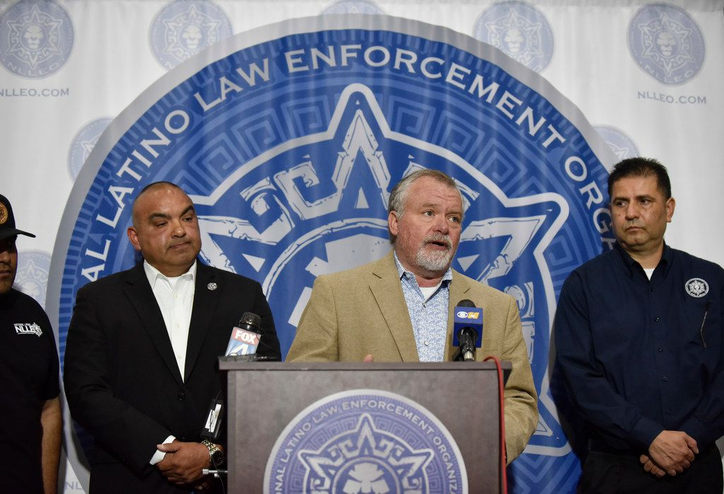 Sgt. Todd Harrison of Austin PD and president of the Combined Law Enforcement Associations of Texas (CLEAT) stands with George Aranda, left, director of the National Latino Law Enforcement Organization (NLLEO), and Richard Santiesteban, right, assistant presidential director of NLLEO, as they call for a vote of no confidence in the leadership of Dallas Chief of Police Renee Hall during a press conference at the headquarters of the National Latino Law Enforcement Organization in Dallas.