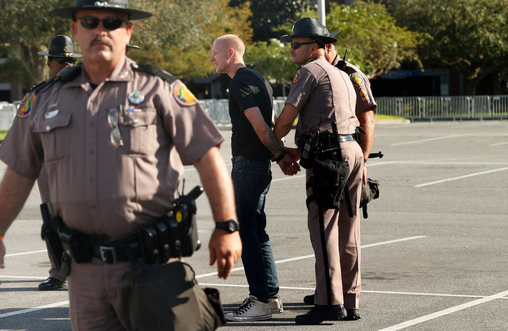 Self-described white nationalist Tyler Tenbrink, of Houston, Texas, is handcuffed by Florida Highway Patrol troopers as the troopers assist his safe departure from a speech by Richard Spencer, who popularized the term 'alt-right',  at the University of Florida campus on October 19, 2017 in Gainesville, Florida. Tenbrink was later arrested, along with friends William Fears and Colton Fears, in relation to a shooting following the speech.
