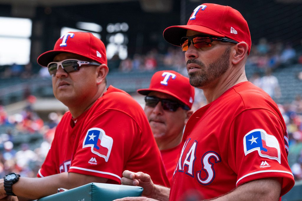 Texas Rangers manager Chris Woodward looks on with pitching coach Julio Rangel (left) and first base coach Hector Ortiz after pitcher Adrian Sampson was called for a balk during the fifth inning against the Seattle Mariners at Globe Life Park on Wednesday, May 22, 2019, in Arlington. (Smiley N. Pool/The Dallas Morning News)
