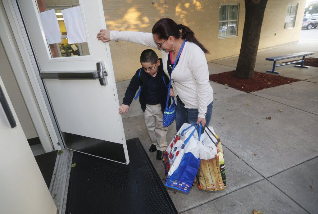 Samuel Garcia, 6, gets help with the door from his mother Irma Garcia, on the first day of school.