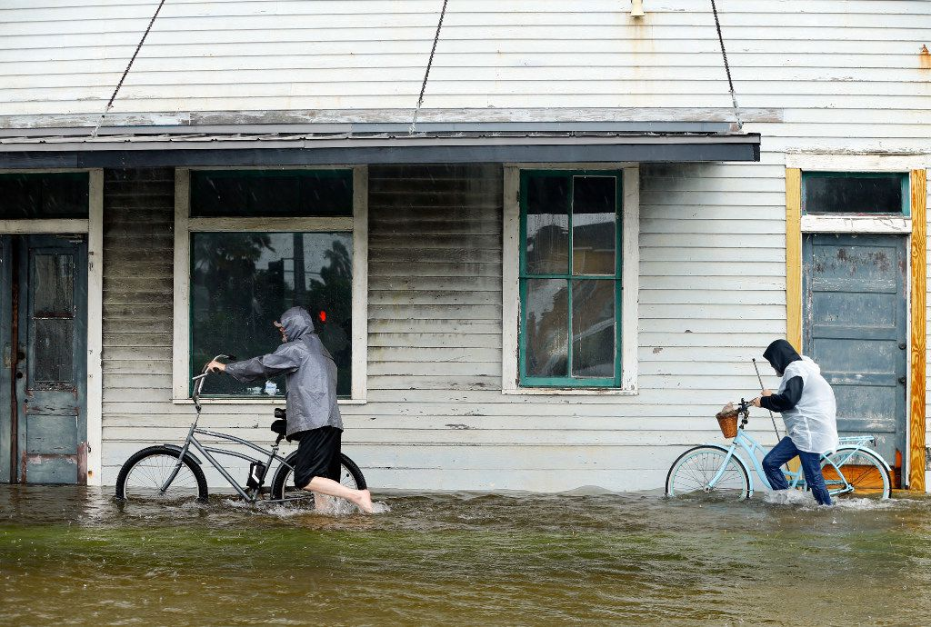 Jim Terrier (left) and Monica Grant of Galveston push their bikes along flooded Broadway Ave. to Henry's for a burrito,Tuesday, August 29, 2017. The city of Galveston, Texas was flooded from punishing overnight rains from Tropical Storm Harvey which passed by the island, Tuesday.(Tom Fox/The Dallas Morning News)