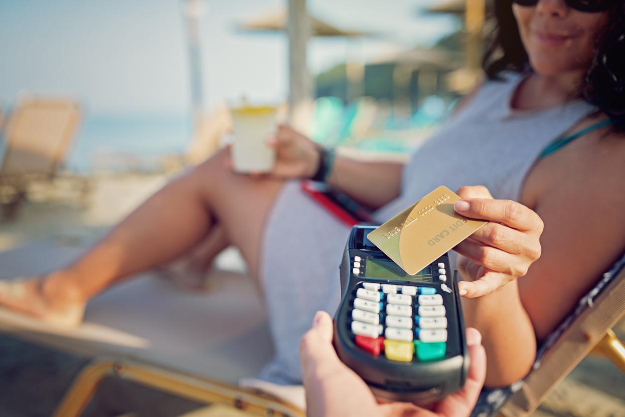 Una mujer paga con una tarjeta de crédito una bebida en un destino turístico.(GETTY IMAGES)