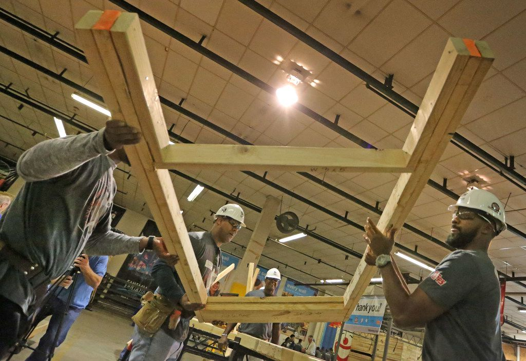 MLB player Chris Young, right, gets some help placing part of a frame Wednesday, Nov. 29, 2017, at a work station as current and former major league baseball players visit the Habitat for Humanity warehouse in Dallas to frame two houses for victims of the Houston floods caused by Hurricane Harvey.