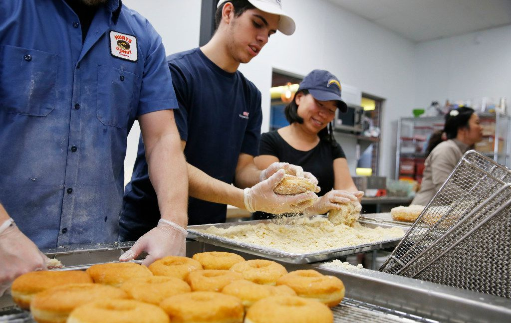 Lynn Ross of Little Elm prepares to apply icing to donuts as Brian Romero and Pam Duncan of Frisco work on applying streusel to donuts at Hurts Donut Co. in Frisco on Tuesday, January 24, 2017. This is Hurts Donut Co.'s first Texas location. (Vernon Bryant/The Dallas Morning News)