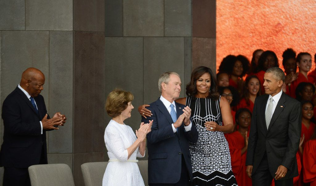 President Barack Obama watches first lady Michelle Obama embracing former president George Bush, accompanied by his wife, former first lady Laura Bush, while participating in the dedication of the National Museum of African American History and Culture.