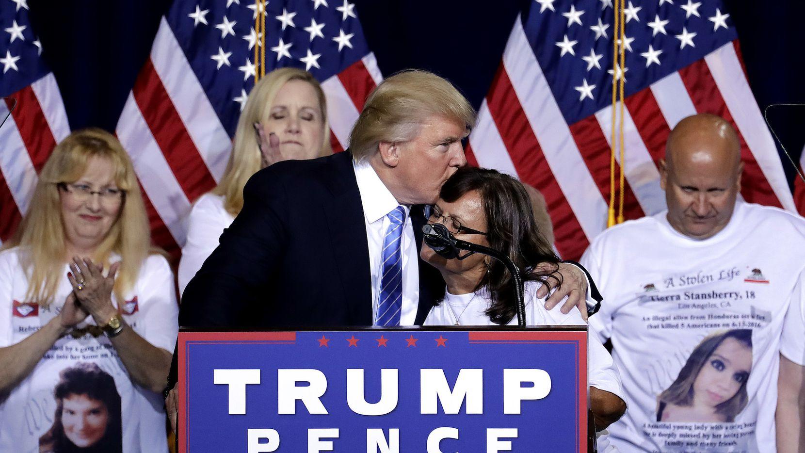 El candidato republicano Donald Trump abraza a una mujer cuyo hijo falleció en un incidente que involucró a un inmigrante indocumentado en Phoenix, Az. (AP).