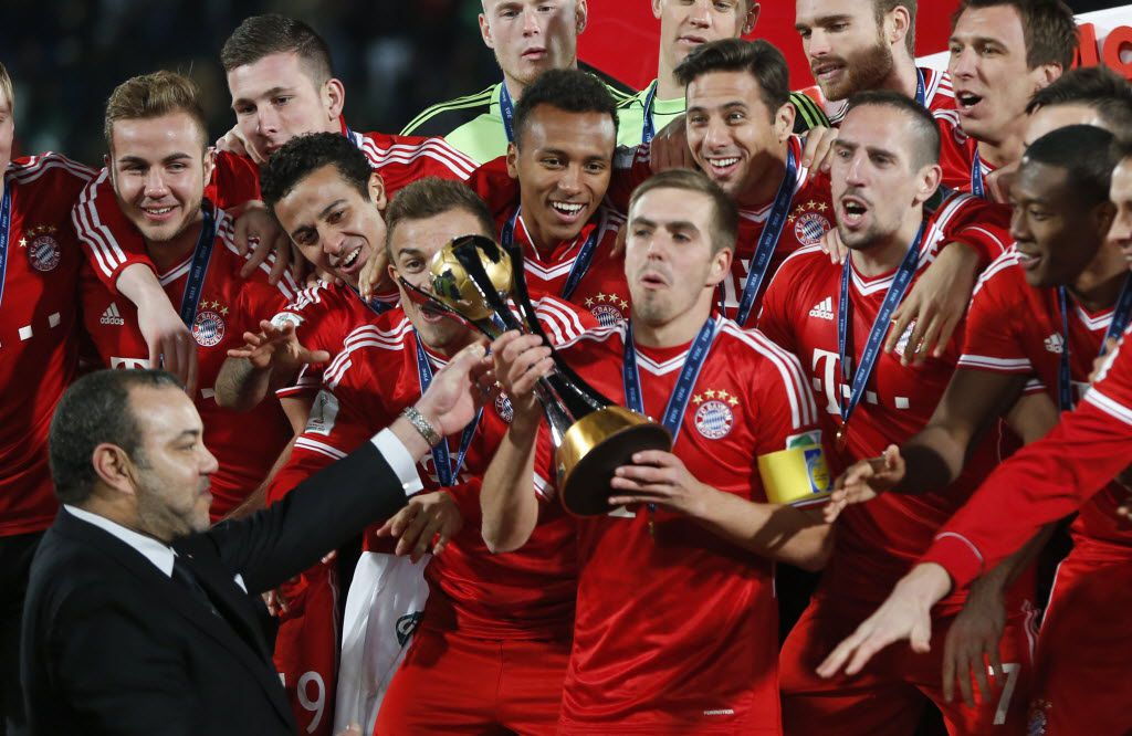Moroccan King Mohammed VI hands over the trophy to Bayern's team captain Philipp Lahm after the final of the soccer Club World Cup between FC Bayern Munich and Raja Casablanca in Marrakech, Morocco, on Dec. 21, 2013.