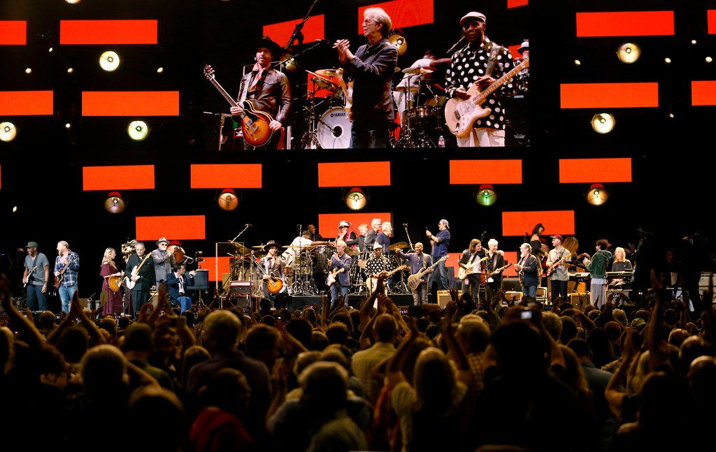 The audience applauds as the final group finale winds down at the end of the Crossroads Guitar Festival on Saturday, Sept. 22, 2019 at the American Airlines Center in downtown Dallas. The stage was filled with at least 14 marquee name performers who took turns soloing. The concert put together by Eric Clapton, which benefits his Crossroads addiction recovery center, took place over two nights with different performers each night. Shown on the screen are Clapton, Doyle Bramhall II (left), of Dallas, and Buddy Guy. (Michael Hamtil/The Dallas Morning News)