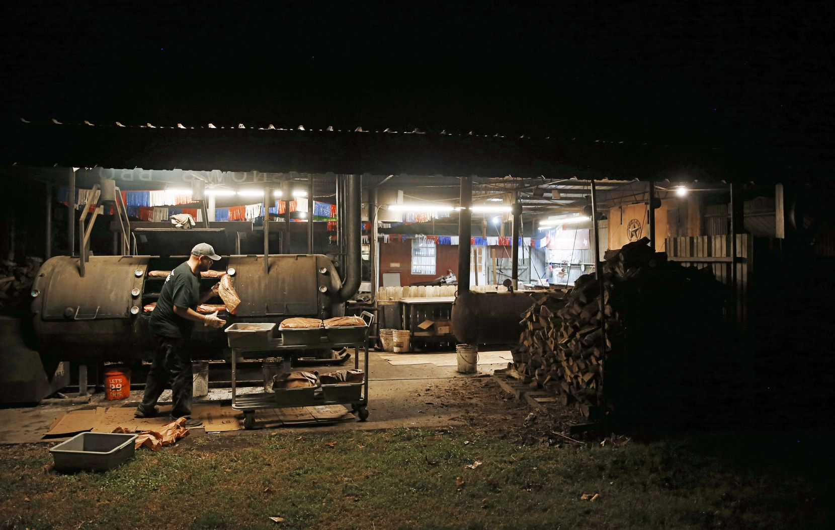 Clay Cowgill works on putting the briskets on the smoker around 10 p.m. at Snow's BBQ in Lexington, Texas, on Aug. 10, 2018.