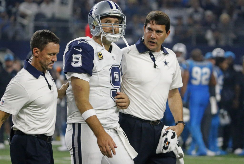 Dallas Cowboys quarterback Tony Romo (9) is helped off the field by trainers Britt Brown, left, and Jim Mauer, right, after being sacked in the third quarter during the Carolina Panthers vs. the Dallas Cowboys NFL football game at AT&T Stadium in Arlington, Texas on Thursday, November 26, 2015. (Louis DeLuca/The Dallas Morning News)