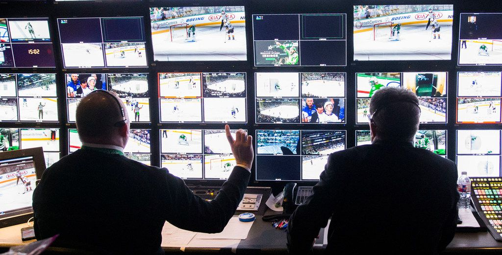 From inside a production truck, producer Mike Leary, left, and director Mark Vittorio produce Fox Sports Southwest's television coverage of a hockey game between the Dallas Stars and the Vancouver Canucks at the American Airlines Center in Dallas on Sunday, March 17, 2019.  (Daniel Carde/The Dallas Morning News)