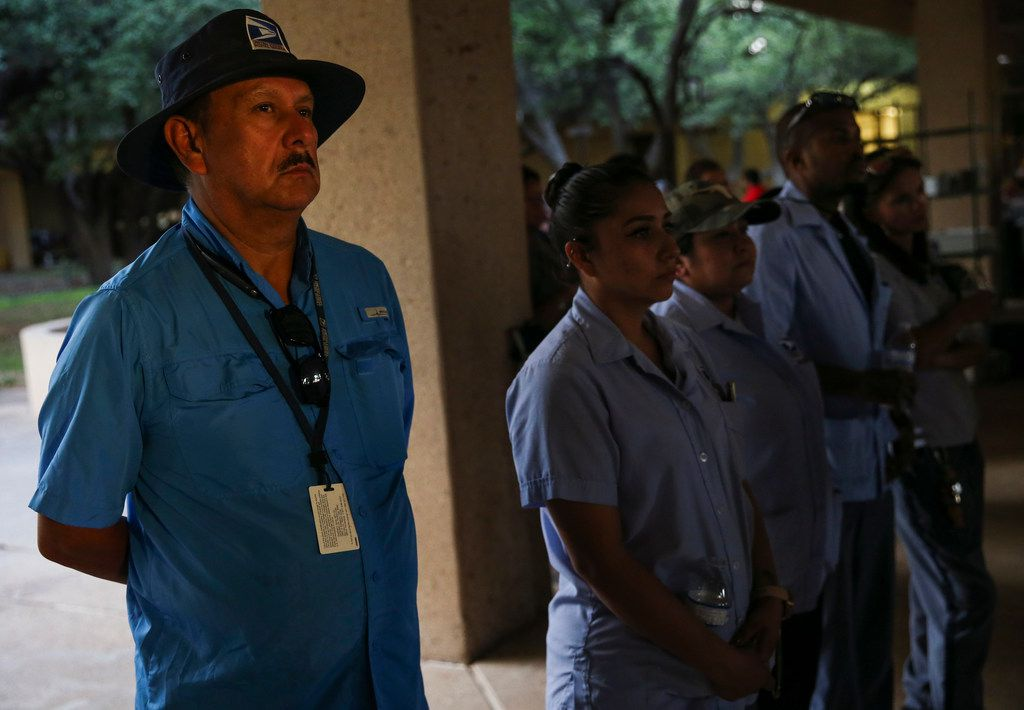 Sergio Bustamante, a U.S. Postal Service worker of Midland, Texas, and other postal workers join community members in gathering for a prayer vigil at the University of Texas Permian Basin on Sunday, Sept. 1, 2019. At least seven people died after more than 20 people were shot Saturday when a gunman hijacked a postal truck and began shooting randomly in the Odessa area of West Texas, authorities say.(Ryan Michalesko/The Dallas Morning News)
