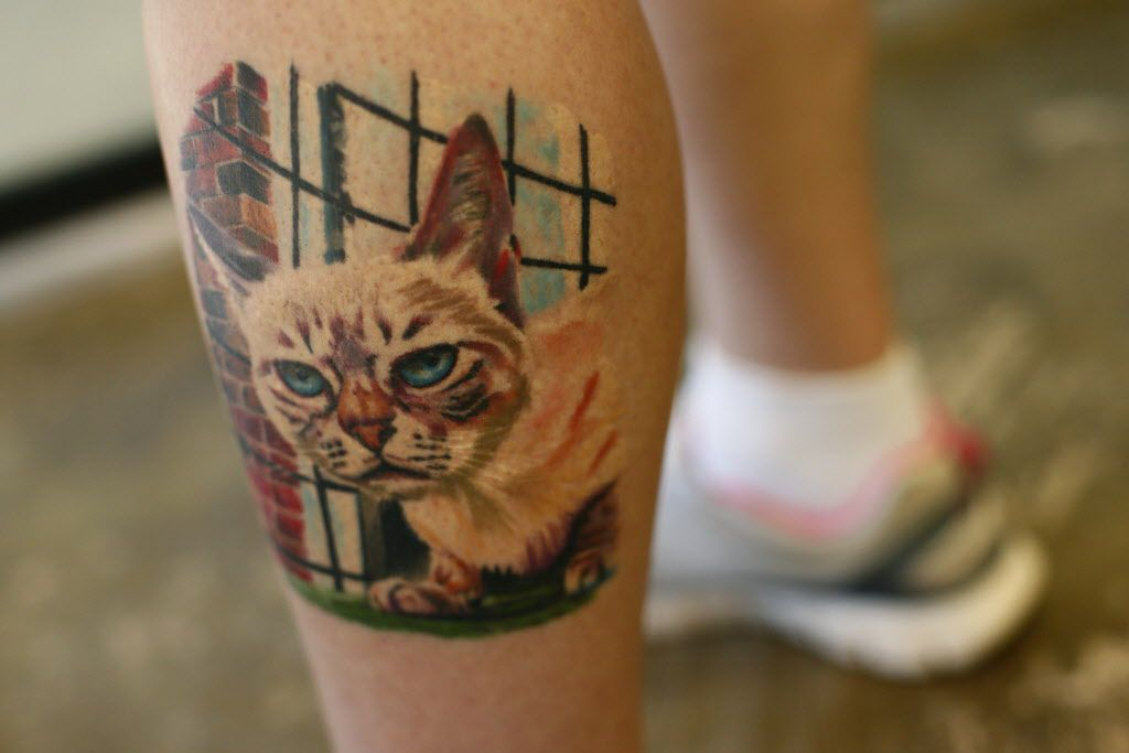 Amy Bender from Oklahoma City, shows her tattoo of her cat, Sauerkraut the famous rescued cat, at  Cat Connection  in Dallas  August 8, 2015.