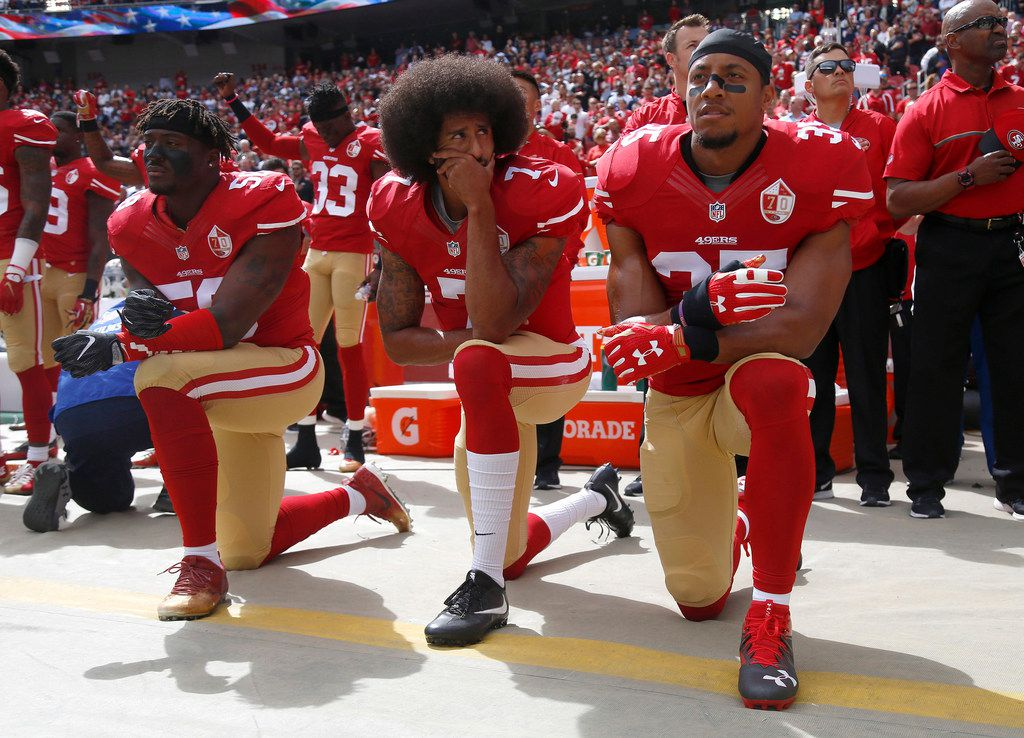From left: San Francisco 49ers players Eli Harold (58), Colin Kaepernick (7) and Eric Reid (35) kneel during the national anthem before their a game against the Dallas Cowboys on Oct. 2, 2016, at Levi's Stadium in Santa Clara, Calif.