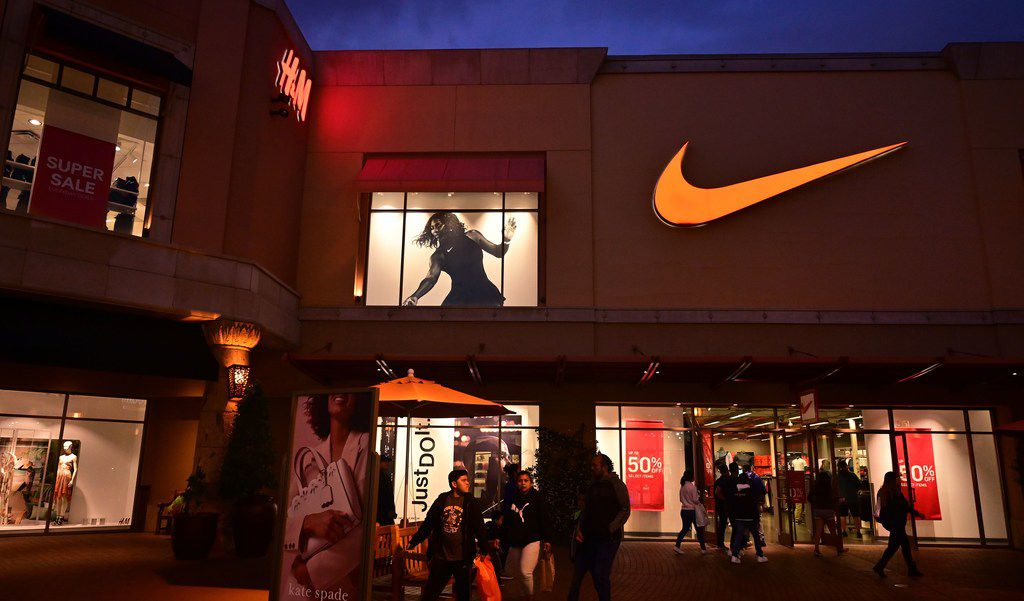 This file photo taken on May 21, 2019, shows shoppers at an outlet mall exit a Nike store in Los Angeles.