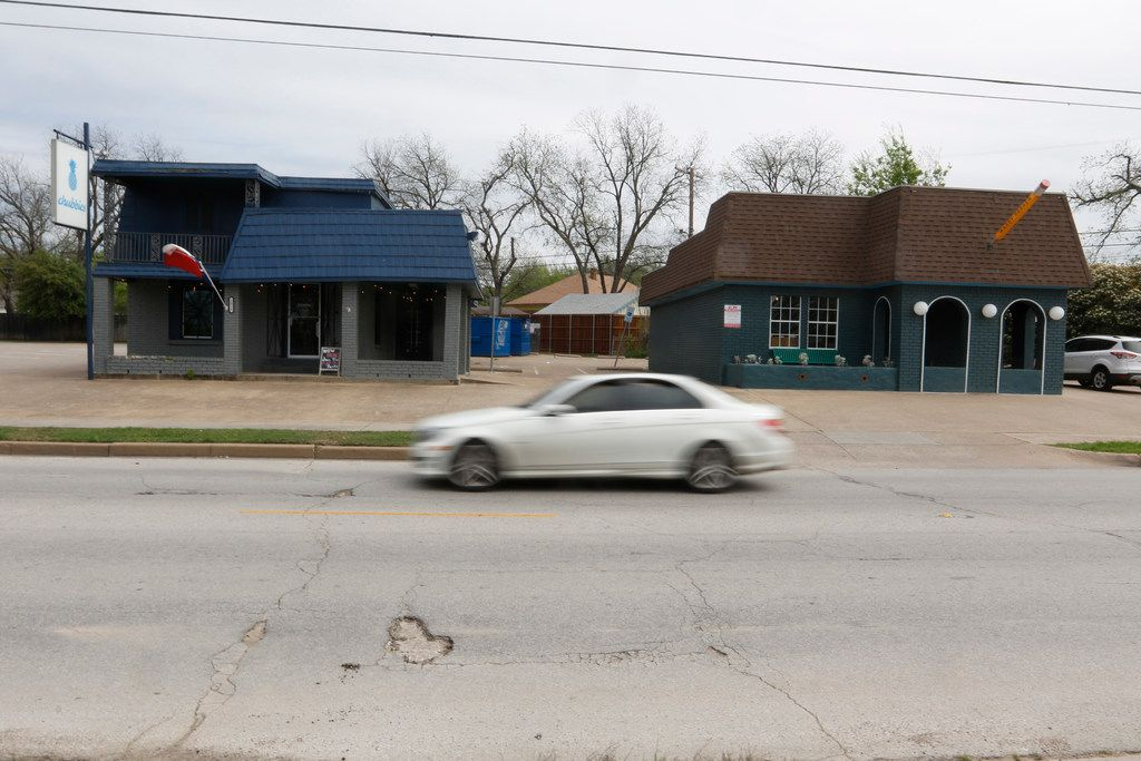 A motorist passes by two buildings on the 2000 block of North Henderson Avenue in Dallas on April 5, 2018 that will be torn down.  A Dallas developer wants to build a mixed-use development on a stretch of land off of Henderson Avenue in Dallas that has been vacant.  (Ron Baselice/Staff Photographer)