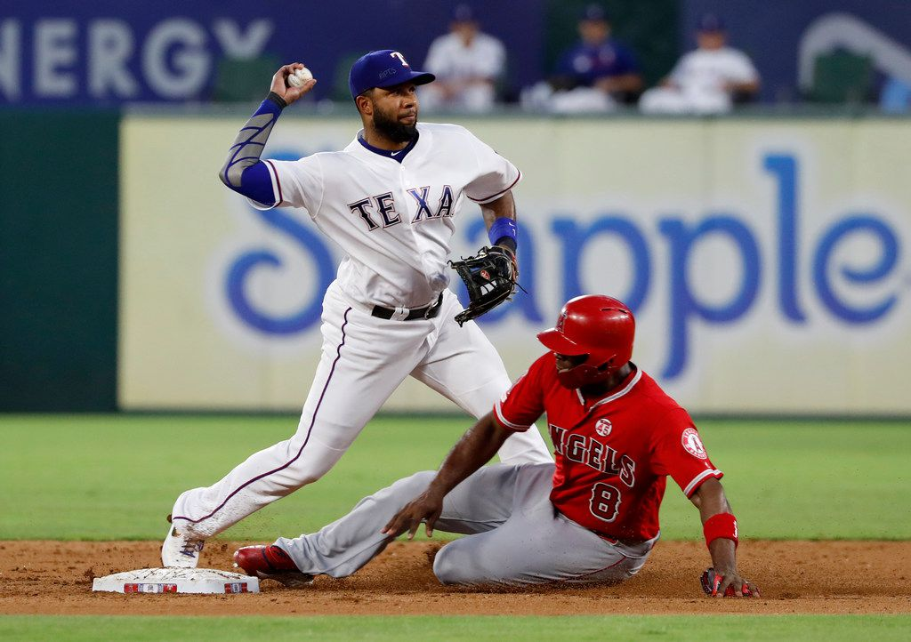 Texas Rangers shortstop Elvis Andrus throws to first for the double play after forcing out Los Angeles Angels' Justin Upton (8) at second during the sixth inning of a baseball game in Arlington, Texas, Wednesday, July 3, 2019. Justin Bour was out at first. (AP Photo/Tony Gutierrez)