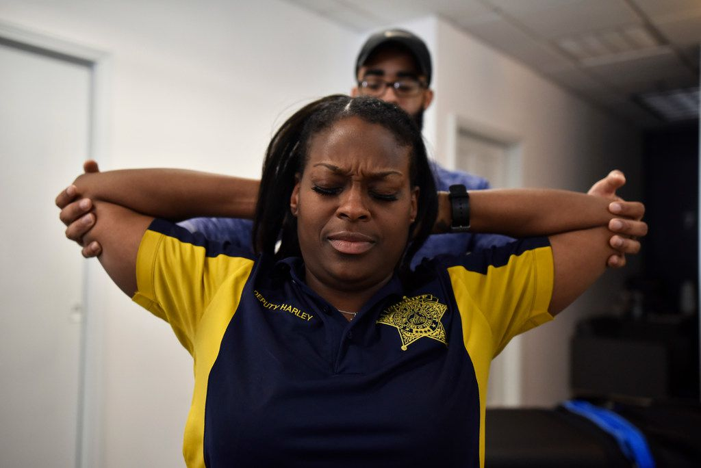 Stretch practitioner Aaron Tobias, center-bottom, works on client Netora Harley, of the Dallas County Sheriff Department, as he pulls on her arms to stretch her during a session at Stretch Zone in Dallas, Wednesday, March 13, 2019. Ben Torres/Special Contributor