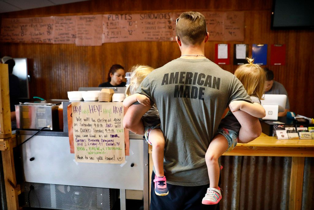 Lee Grounds of Barry, Texas, holds his twin 2-year-old daughters Leighton (left) and Langston while waiting on his order at Flores Barbecue in Whitney. He says he regularly drives more than 40 miles for the barbecue.