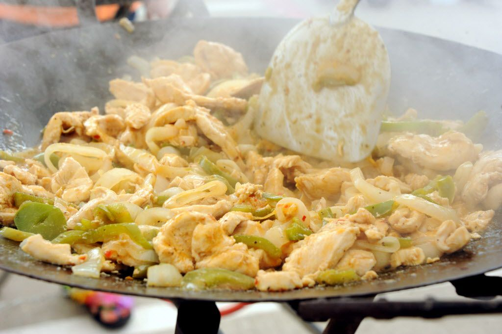 Fans grill chicken fajitas at the Jimmy Buffett tailgate party at Toyota Stadium in Frisco, TX on May 30, 2015.
