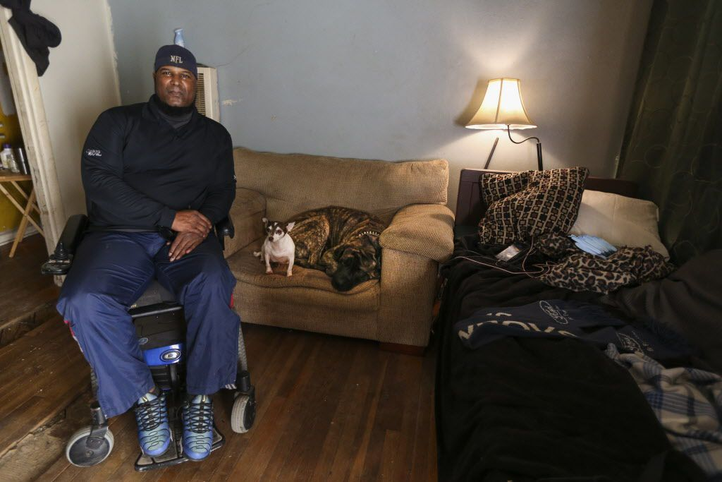 """Mark Booker, alongside his dogs Butter (center) and Rick, at his Hamilton Park home Tuesday.  """"I grew up in this place,"""" Booker said. """"This was my mom and dad's house. It's been in the family all my life."""""""