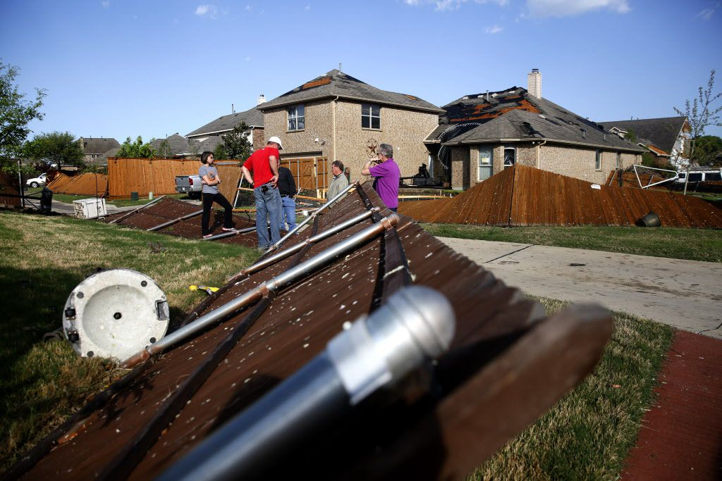 Homeowners stand in their backyard along a storm damaged fence following a thunderstorm in the early hours of the morning in Rockwall, Texas on Wednesday, March 29, 2017. (Rose Baca/The Dallas Morning News)
