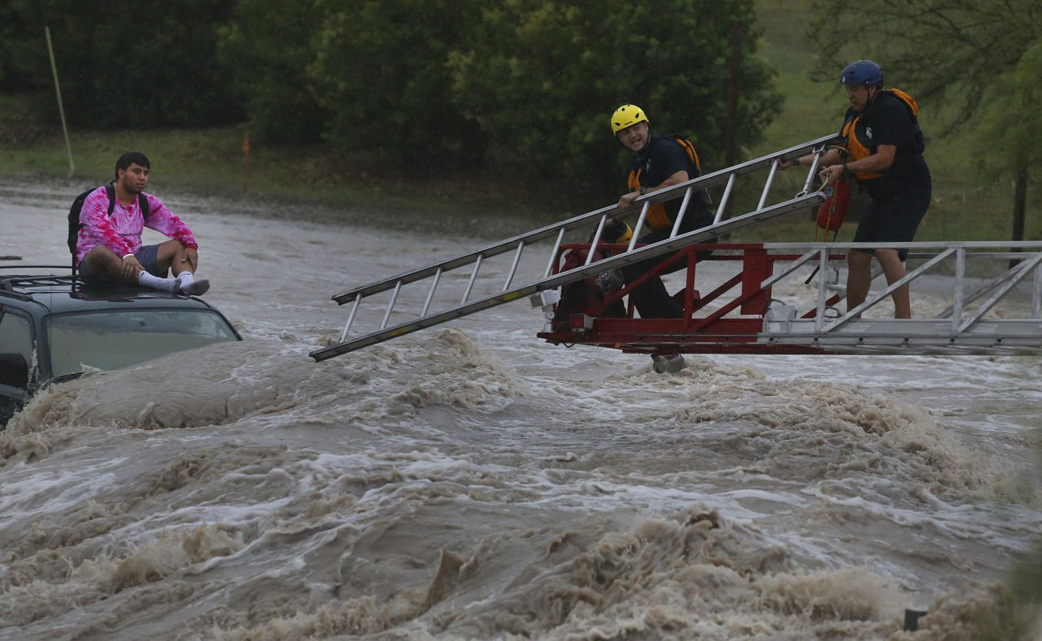 San Antonio firefighters rescue a man Monday August 7, 2017 from the roof of his SUV at Pinn Road and State Highway 151 after rain swept through the San Antonio area. The man was not injured.