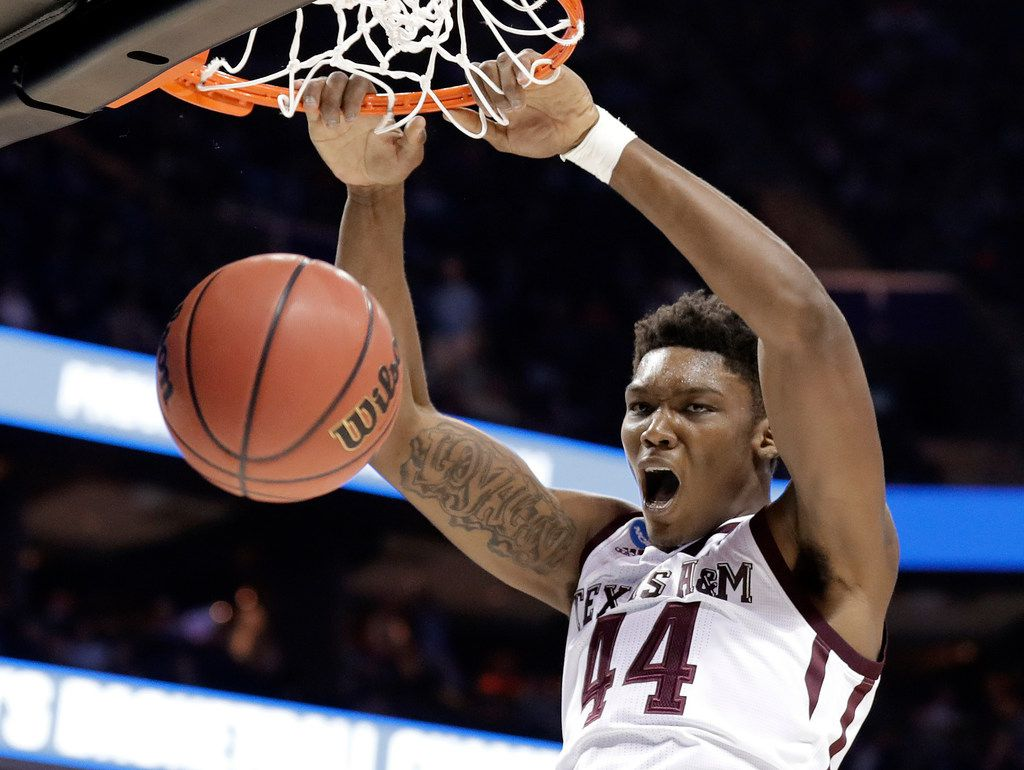FILE - In this March 16, 2018, file photo, Texas A&M's Robert Williams dunks against Providence during the second half of a first-round game in the NCAA men's college basketball tournament in Charlotte, N.C. Robert Williams is a possible pick in Thursday's NBA Draft. (AP Photo/Gerry Broome, File)