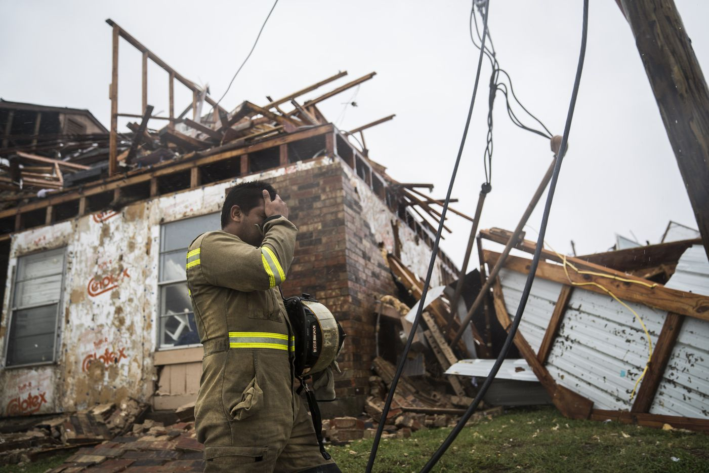 A firefighter wipes his face as he searches for survivors at an apartment complex in Rockport, Texas, as Hurricane Harvey hits the state's coast on Saturday. Must credit: Washington Post photo by Jabin Botsford
