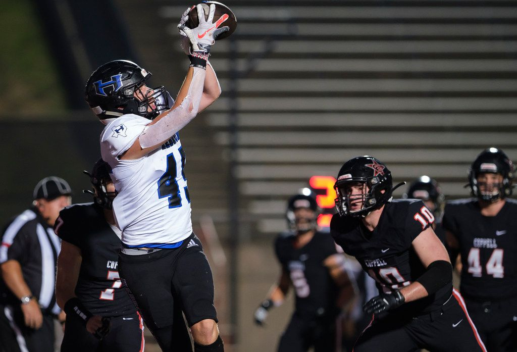 Hebron tight end  Ben Rutherford (45) catches a touchdown pass as Coppell defensive back Gavin Osteen (7) and linebacker Payton Rosenbaum (10) defend during the first half of a high school football game on Friday, Oct. 4, 2019, in Coppell, Texas. (Smiley N. Pool/The Dallas Morning News)