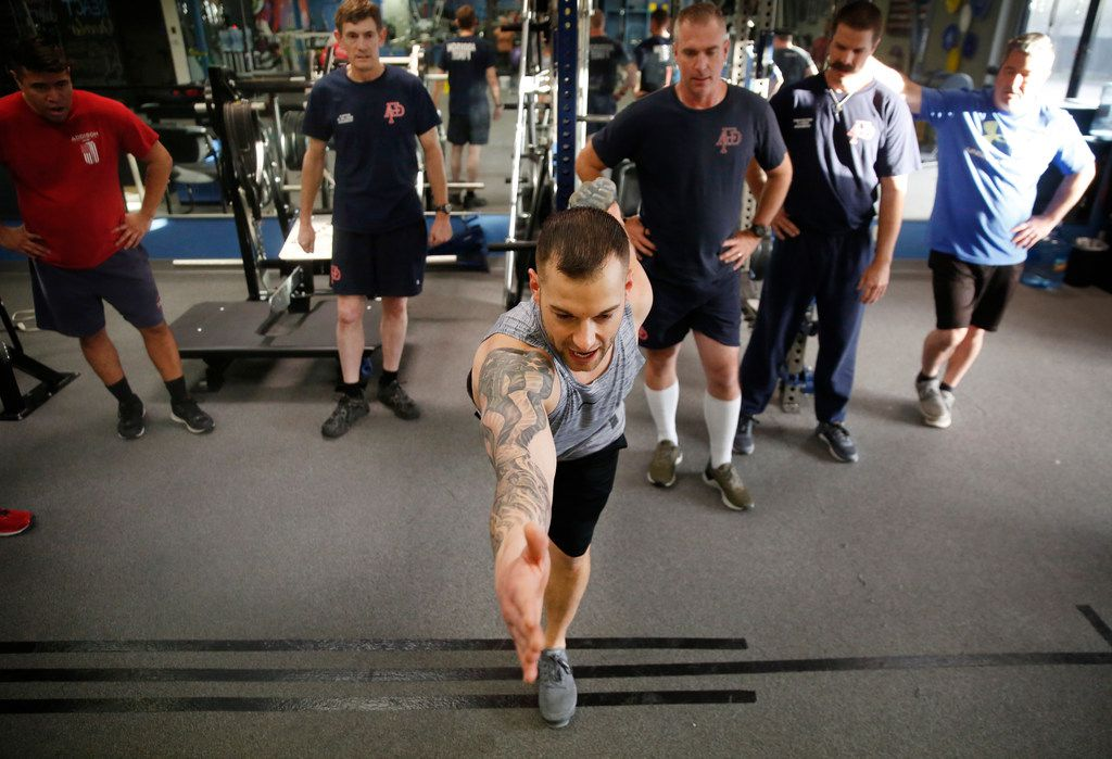 Ryan Bachik, REACT co-founder and program director of tactical operations, leads a group of Addison firefighters at REACT gym in Addison, Texas on Thursday, Jan. 24, 2019. The gym is now offering a free injury prevention training program to Addison first responders. (Rose Baca/Staff Photographer)
