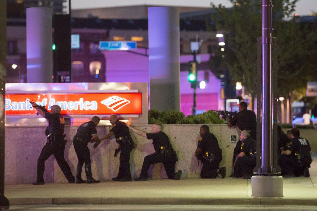 Dallas Police take up position along a wall at the corner of Lamar at Main as they train their weapons toward the El Centro campus after shots were fired during a Black Lives Matter rally in downtown Dallas on Thursday, July 7, 2016. As the rally and march were winding down, Micah Xavier Johnson, 25, opened fire in an attack that killed five police officers and wounded seven other officers and two civilians. (Smiley N. Pool/The Dallas Morning News)