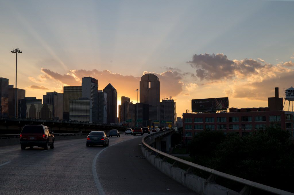 The sun sets on the Dallas skyline on the ramp from Interstate 30 west to I-345 north, an elevated highway that divides downtown Dallas (left) from Deep Ellum. (Ting Shen/The Dallas Morning News)